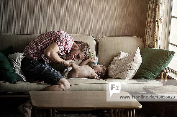 Vater küsst zu Hause auf dem Sofa die Füße eines kleinen Jungen
