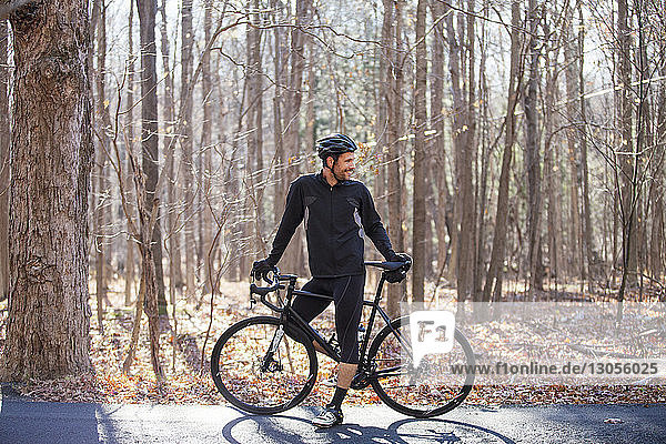 Cyclist standing by bicycle on road at forest