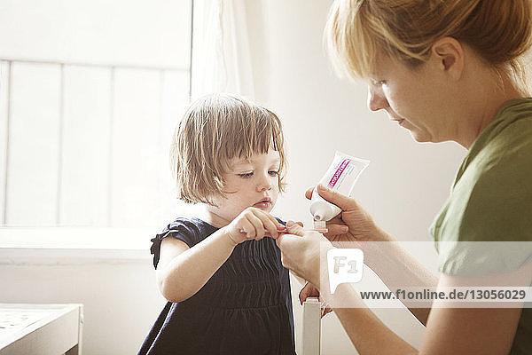 Mutter hilft Tochter beim Zähneputzen zu Hause