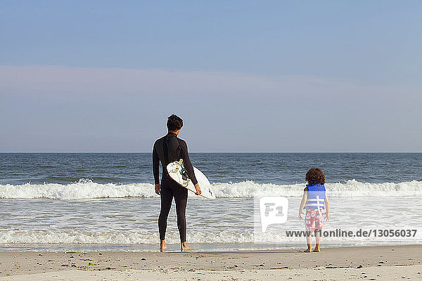 Rear view of father and son standing on shore at beach