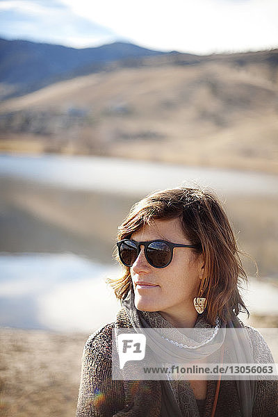 Woman in sunglasses against mountain on sunny day