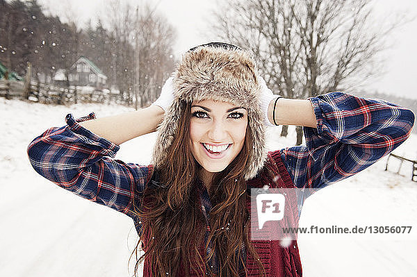 Portrait of cheerful woman standing with hands behind head on snow covered field