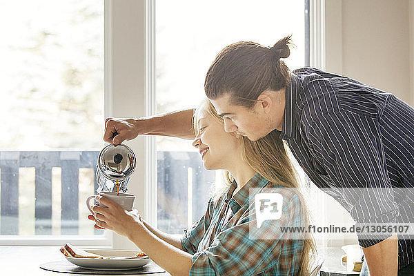 Mann gießt Kaffee in Tasse für Freundin zu Hause