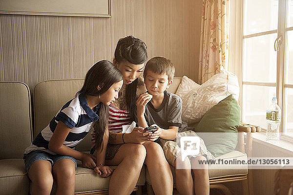 Mother and children using phone while sitting on sofa at home