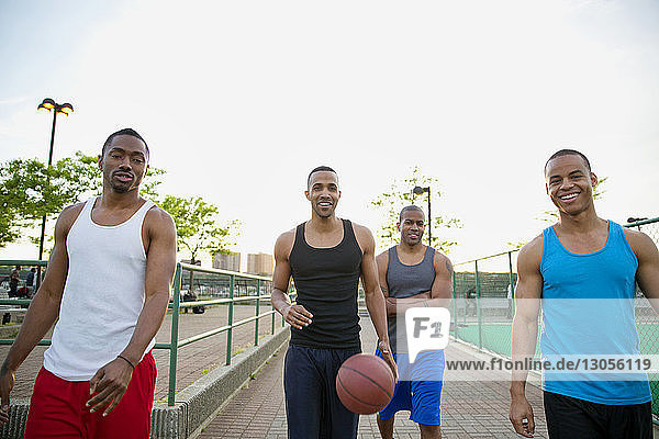 Portrait of happy friends with basketball walking on footpath in park