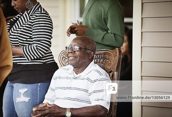 Glücklicher älterer Mann sitzt auf Stuhl von Frau  die auf der Veranda steht