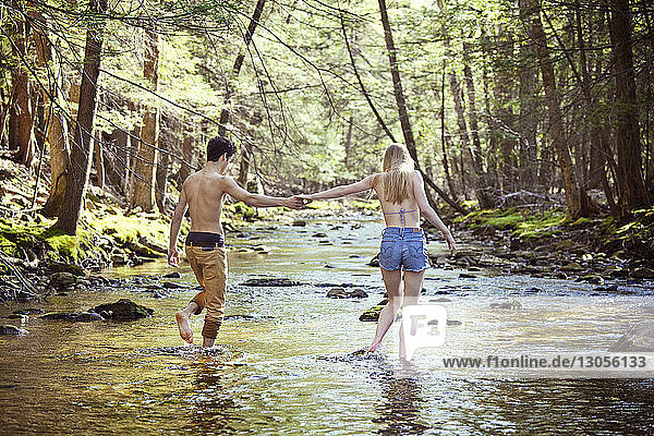 Young couple holding hands while walking in stream