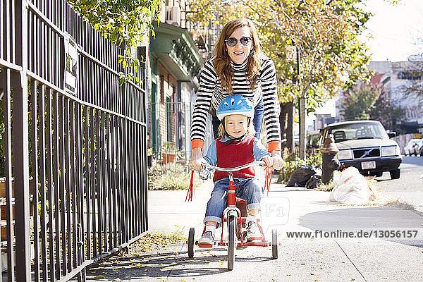 Verspielte Mutter mit Sohn radelt auf Wanderweg