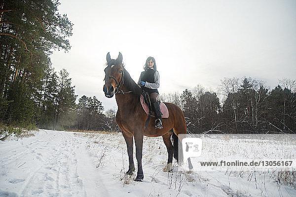 Frau reitet Pferd auf schneebedecktem Feld gegen den Himmel