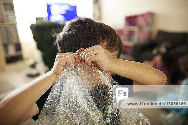 Boy playing with bubble wrap at home
