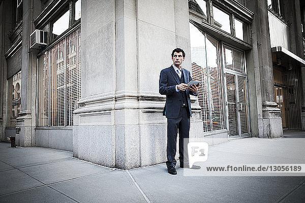 Geschäftsmann hält digitales Tablet und stellt sich gegen Gebäude