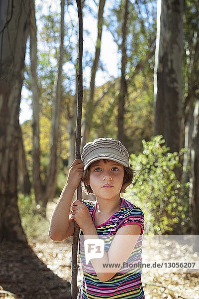 Portrait of girl holding stick while standing in forest