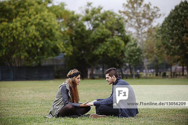 Paar hält Hände  während es auf einem Grasfeld im Park sitzt