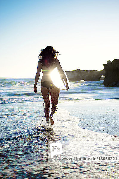 Rear view of woman with surfboard walking on shore at beach