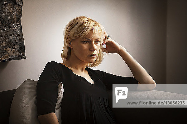 Thoughtful woman with hand in hair sitting on sofa at home