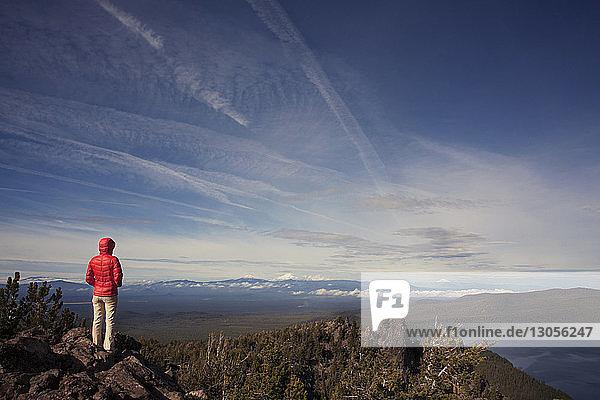 Rückansicht einer Frau  die auf einem Berg vor blauem Himmel steht
