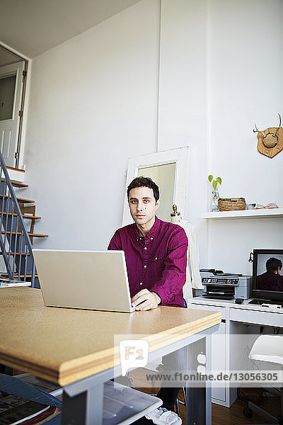 Portrait of businessman using laptop at table in creative office