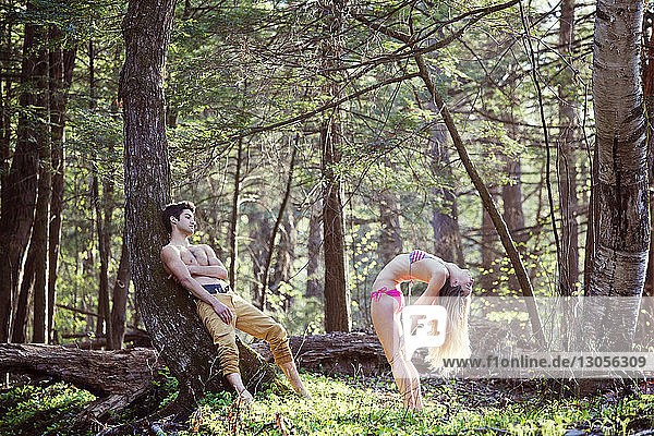 Man looking at woman bending backwards in forest