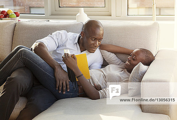 Man looking at woman reading book while lying on sofa at home