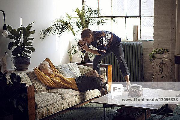 Mann filmt Frau  die zu Hause auf dem Sofa liegt