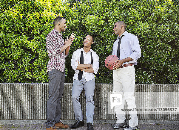 Smiling man holding basketball while talking with friends against plants