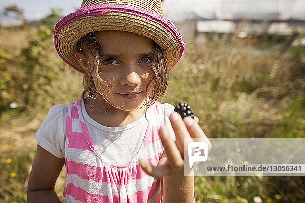 Portrait of girl holding blackberry on field