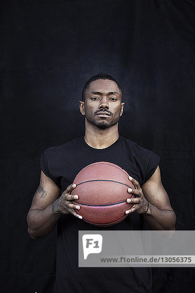 Portrait of sportsman holding basketball while standing against black wall