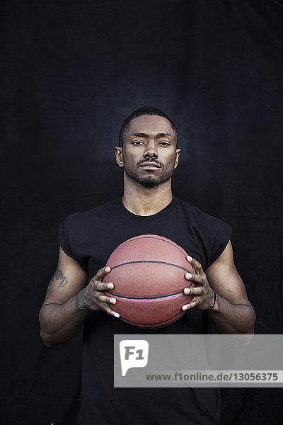 Porträt eines Sportlers  der Basketball in der Hand hält  während er gegen eine schwarze Wand steht