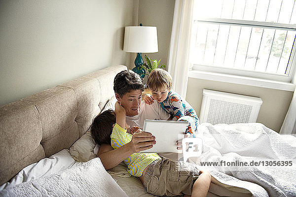 Father showing tablet computer to sons on bed at home