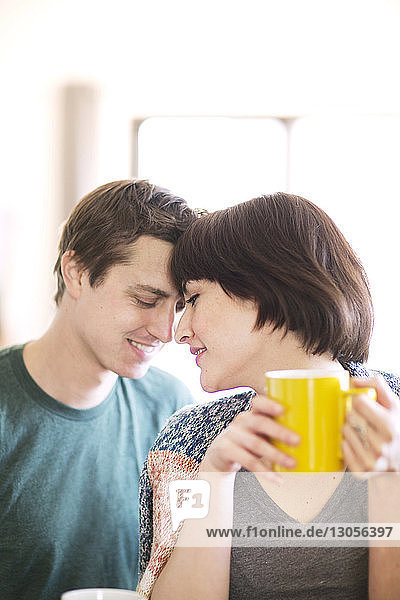 Woman drinking coffee while sitting with boyfriend at home