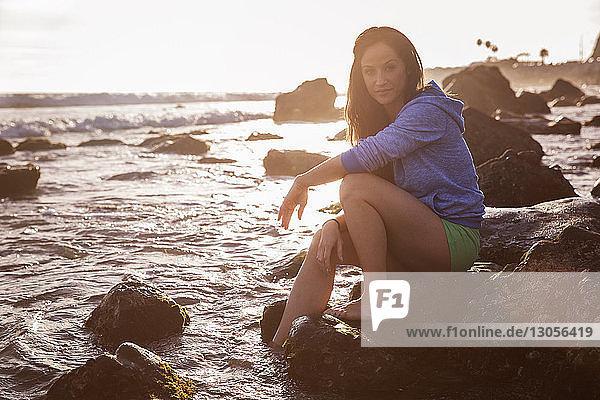 Porträt einer selbstbewussten Frau  die auf einem Felsen am Strand sitzt