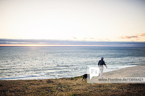 Man and dog walking on field by sea against sky