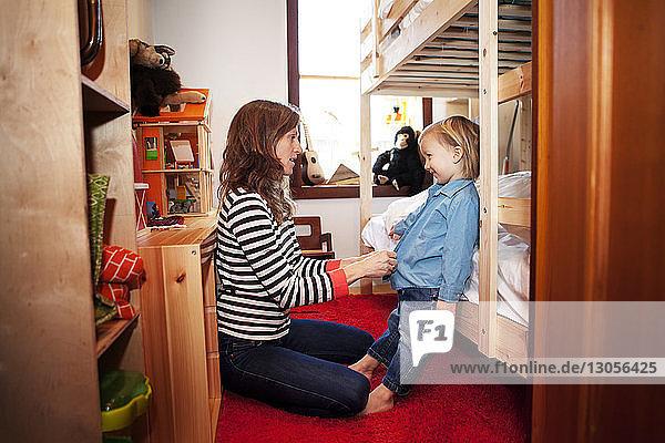 Seitenansicht der Mutter beim Ankleiden des Sohnes im Schlafzimmer