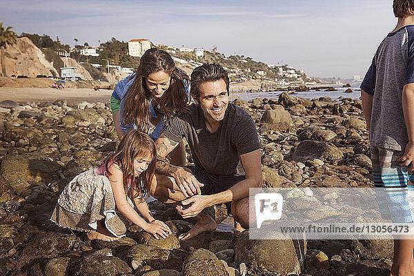 Family enjoying at beach during sunset