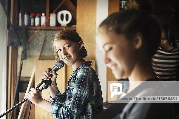 Mädchen sieht Freundin beim Singen im Aufnahmestudio an