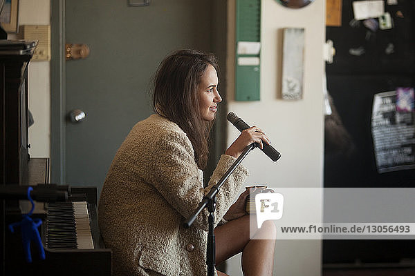 Side view of woman holding microphone while sitting at home