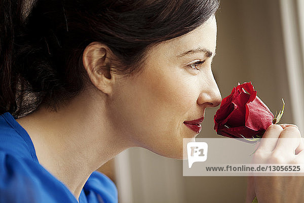 Close-up of woman smelling red rose