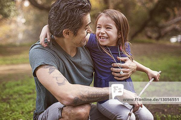 Glücklicher Vater sieht Tochter an