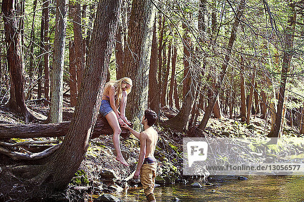 Man holding hand of girlfriend while standing in stream