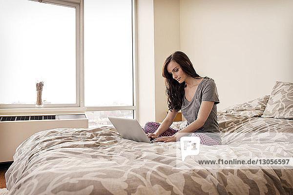 Seitenansicht einer Frau  die einen Laptop auf dem Bett in einem hell erleuchteten Schlafzimmer benutzt