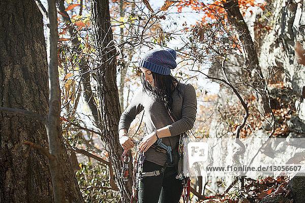 Frau stellt Sicherheitsgurt ein  während sie an Bäumen steht