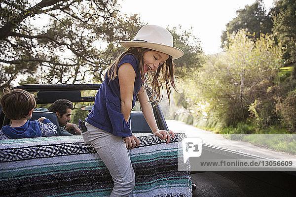 Mädchen spielt  während die Familie im Geländewagen sitzt