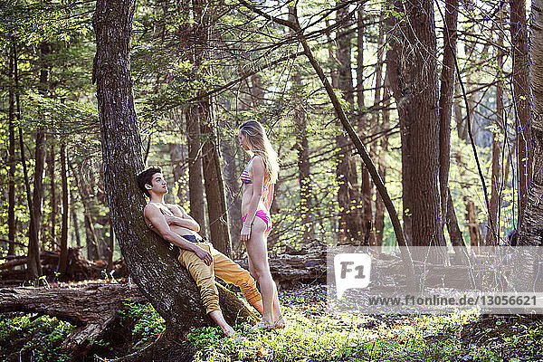 Couple looking at each other while standing in forest