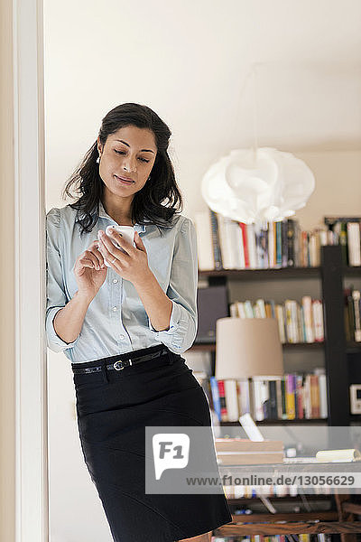 Businesswoman using smart phone at home