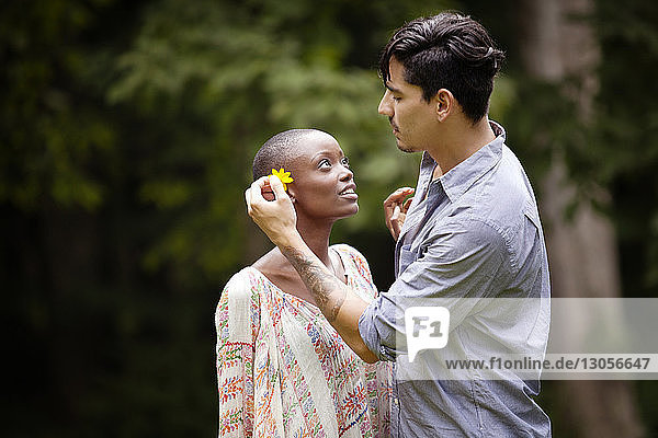 Side view of man putting flower in woman's ear