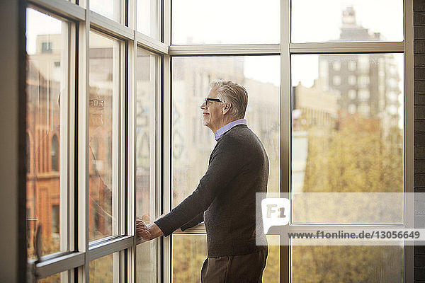 Side view of smiling man standing by window at home
