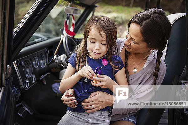Glückliche Mutter schaut auf Mädchen  das im Pick-up orange schält