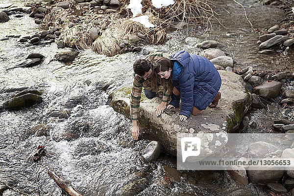 Couple touching river water while kneeling on rock
