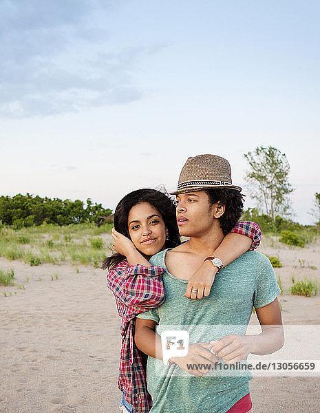 Porträt einer Freundin  die einen Mann umarmt  während sie am Strand gegen den Himmel steht