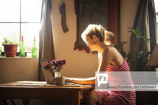 Frau benutzt Laptop-Computer  während sie am Tisch sitzt